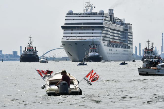 Un militant écologistemanifeste à bord d'un petit bateau contre la présence de navires de croisière dans le lagon, à Venise (Italie), le 5 juin 2021.