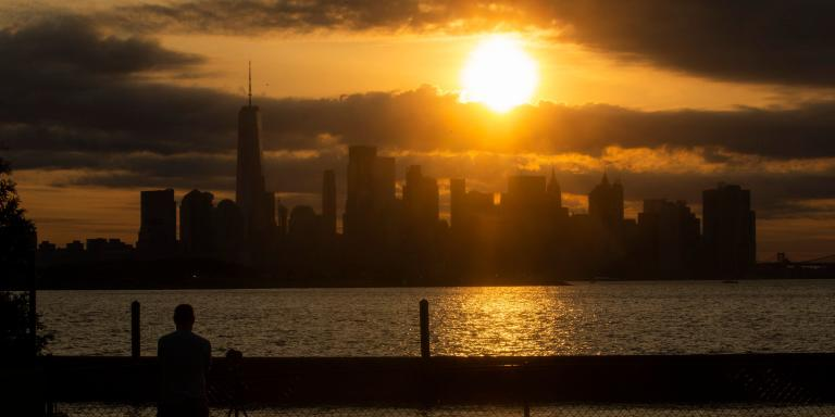 The New York skyline is seen as the Moon partially covers the sun during a partial solar eclipse on June 10, 2021 seen from Jersey City, New Jersey.  Northeast states in the U.S. will see a rare eclipsed sunrise, while in other parts of the Northern Hemisphere, this annular eclipse will be seen as a visible thin outer ring of the sun's disk that is not completely covered by the smaller dark disk of the moon, a so-called