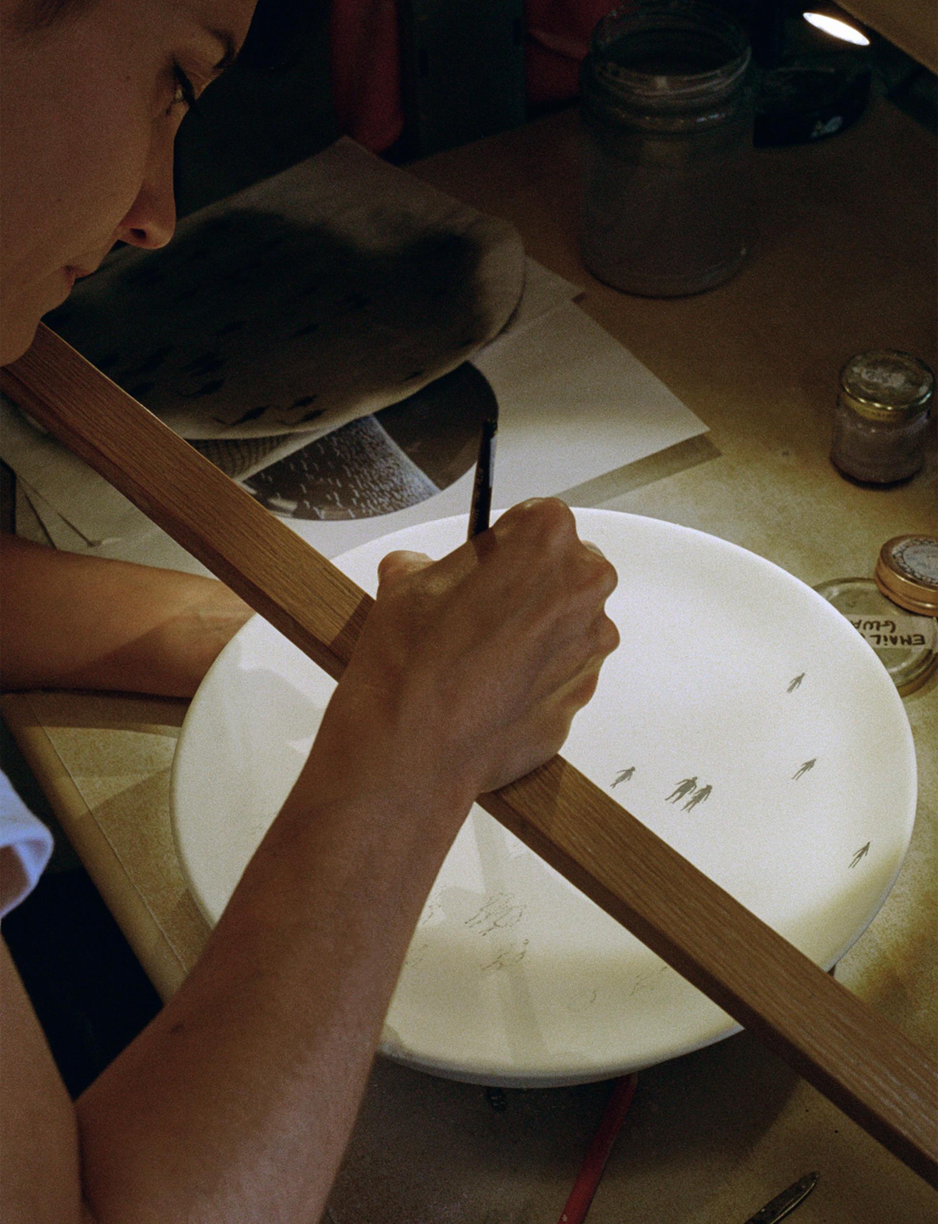 Pour améliorer la précision de son geste, Carole Georges repose son poignet sur une baguette de bois. Une technique déjà utilisée par ses aïeux.