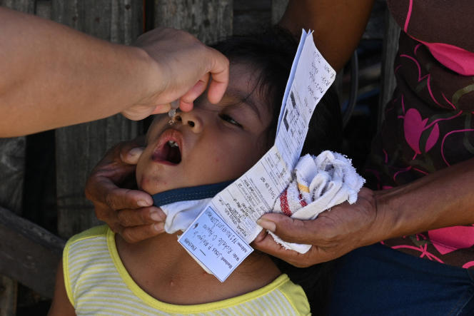 A municipal health worker applies drops of a polio vaccine to a child in San Jose del Monte, Bulacan province, north of Manila, September 21, 2020.