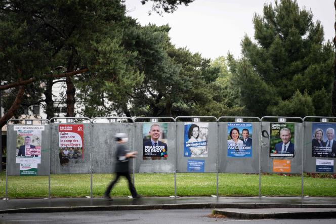 A woman walks past electoral panels ahead of the upcoming French regional elections, on June 3, 2021 in Nantes, western France. / AFP / LOIC VENANCE