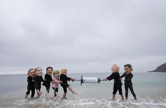 Des militants d'Oxfam simulant au bord de l'eau une bataille autour d'une seringue géante, Oxfam plaidant pour la suspension des brevets, qui permettrait une production en masse des vaccins anti-Covid-19,à Swanpool Beach, à Falmouth, en Cornouailles, le 11 juin 2021.