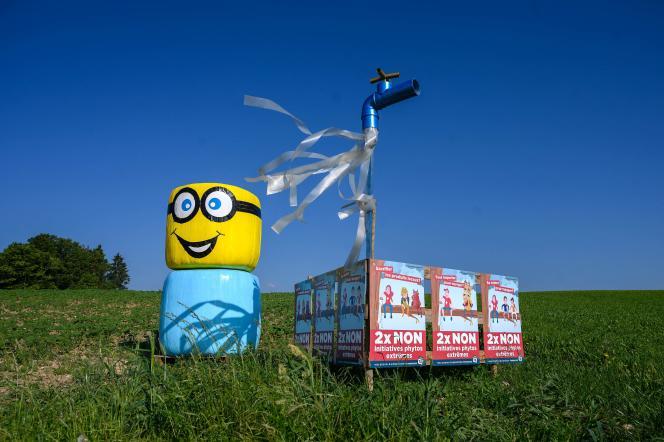 Le 11 juin 2021, une botte de paille représentant un personnage à côté d'une affiche électorale sur laquelle on peut lire en français : «Deux fois non aux initiatives phytosanitaires extrêmes», à Senarclens, en Suisse occidentale.