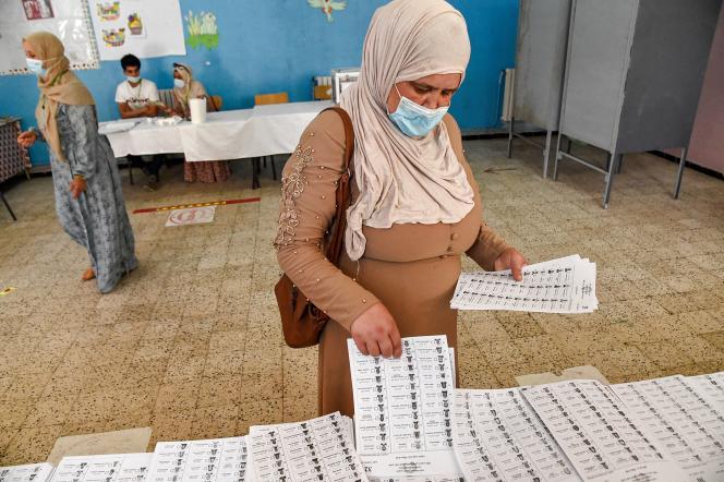 Une femme ramasse un bulletin de vote alors qu'elle se prépare à voter dans un bureau de vote à Bouchaoui, dans la banlieue ouest d'Alger (Algérie), le 12 juin 2021, lors des élections législatives de 2021.