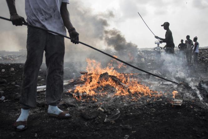 Des jeunes hommes brûlent des déchets électroniques dans la décharge du bidonville d'Agbogbloshie, au Ghana, le 29 novembre 2017.