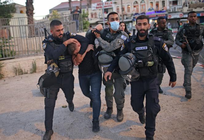 Des forces de police israéliennes arrêtent un Palestinien près de la porte de Damas, à Jérusalem-Est, alors que des ultranationalistes participent à la Marche des drapeaux près de la vieille ville de Jérusalem, le 15juin 2021.