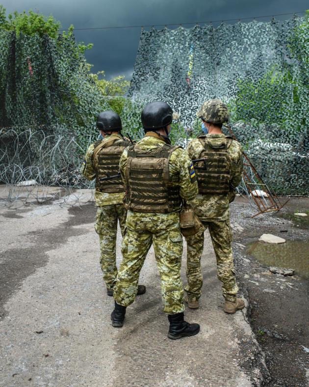 Trois gardes-frontières ukrainiens accueillent les rares candidats à la traversée du checkpoint de Maïorsk, ouvert côté ukrainien mais maintenu fermé par les autorités de l'autoproclamée République populaire de Donetsk, le 3 juin 2021.