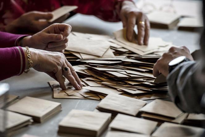 Des assesseurs trient les bulletins de vote, à Valence (Drôme), enmars2015.