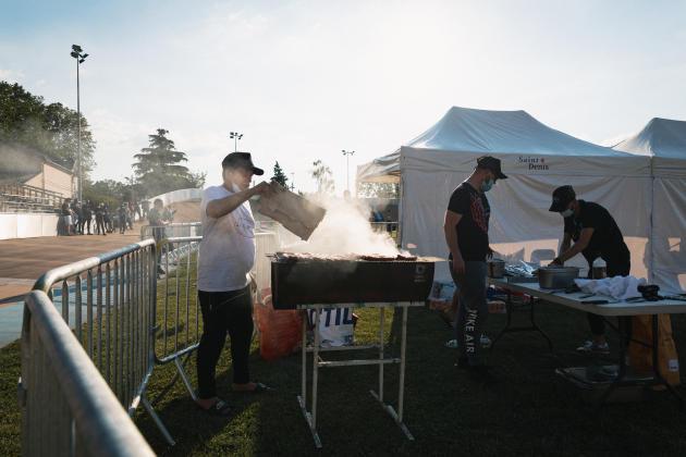 Derrière le stand où l'association 7 Dreams vend des sandwichs et des boissons. Les bénévoles préparent les merguez.