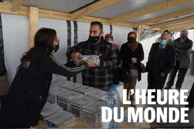 La bénévole d'une association humanitaire donne la nourriture à des Libanais dans le besoin, à Beyrouth, le 24 mars 2021.
