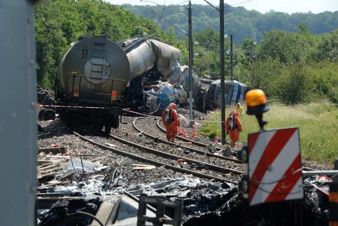 Des sapeurs-pompiers inspectent le lieu de l'accident, après la collision entre un train de fret transportant de l'acide phosphorique et un convoi exceptionnel transportant un bateau, le 16 juin 2021 à l'entrée du village de Rumigny (Ardennes).