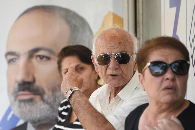 Des Arméniens attendent leur bus, devant une affiche électorale en faveur du premier ministre, Nikol Pachinian, le 16 juin 2021.