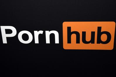 (FILES) In this file photo taken on January 24, 2018 a Pornhub logo is displayed at the company's booth at the 2018 AVN Adult Entertainment Expo at the Hard Rock Hotel & Casino in Las Vegas, Nevada. A complaint was filed on June 17, 2021 in California by 34 women who accuse the website Pornhub and its parent company of having knowingly put online videos where they are victims of rape and other sexual abuse, including when they were minors. / AFP / GETTY IMAGES NORTH AMERICA / Ethan Miller