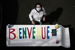 Un membre du personnel de l'Institut privé Sainte-Geneviève prépare une banderole de bienvenue, à Paris, en mai 2020.