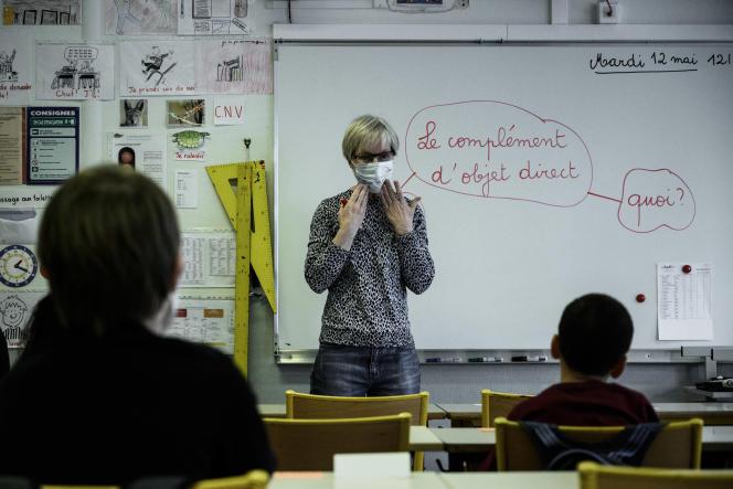 Un enseignant utilise un masque facial comme exemple lors d'un cours à l'école privée Institut Sainte-Geneviève, à Paris, le 12 mai 2020.