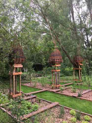 Ces ruches en saule tressé, matériau traditionnel des hortillonnages, accueillent des colonies d'abeilles, dont la présence est essentielle à la pollinisation des plantes nourricières.