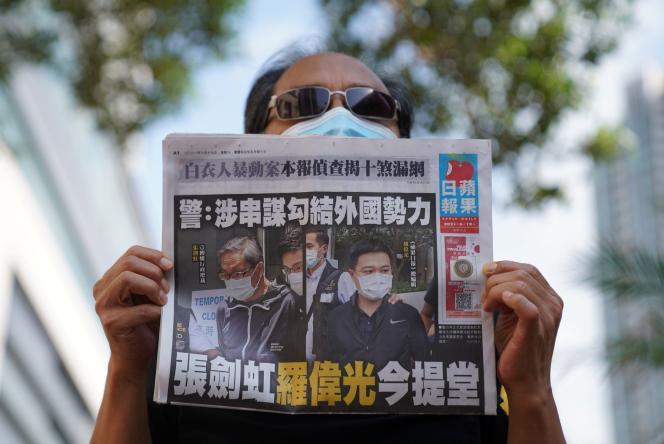 Un homme tient une copie du « Apple Daily», devant le tribunal de Kowloon West, après l'inculpation de deux dirigeants du journal pro démocratie, à Hongkong, le 19 juin 2021.