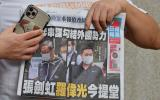 A supporter of two executives from Hong Kong's pro-democracy Apple Daily newspaper, chief editor Ryan Law and CEO Cheung Kim-hung, holds up a copy of the newspaper during a protest outside court in Hong Kong on June 19, 2021, after the two were charged with collusion over their newspaper's coverage after authorities deployed a sweeping security law. / AFP / Peter PARKS