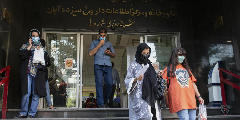 People are seen at the entrance of the central pharmacy called Sizdah-e Aban in Tehran, Iran, on June 22, 202.