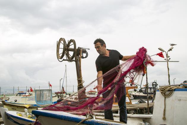 Uğur Kıran démêle ses filets qui sont abîmés par le «mucilage», sur l'île d'Heybeliada, près d'Istanbul,le 14 juin 2021. L'activité du pêcheur est très affectée par la pollution de la mer de Marmara.