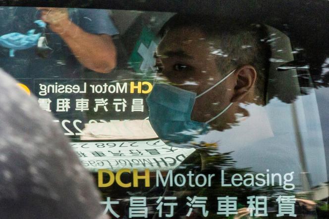 Tong Ying-kit, accusé d'avoir délibérément dirigé sa moto vers un groupe de policiers, muni d'une banderole appelant à« libérer Hongkong», arrive au tribunal, le 6 juillet 2020.