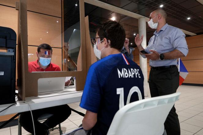 Un supporteur des Bleus s'enregistre avant de recevoir une dose de vaccin Pfizer, le 23 juin 2021 à Poissy.