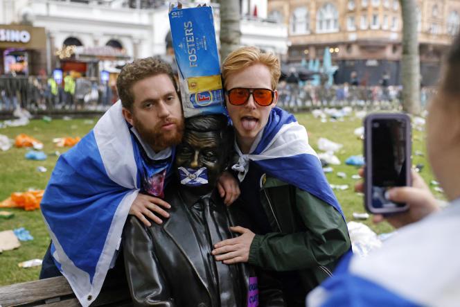 Des supporteurs écossais posent devant la statue de Mister Bean à Leicester Square, le 18 juin 2021, à Londres.