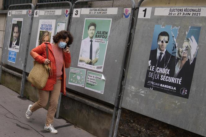 Une femme passe devant des affiches de campagne pour les élections régionales, à Paris, le 24 juin 2021.