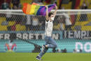 A fan with a LGBT pride flag runs on the pitch during the national anthems before the Euro 2020 soccer championship group F match between Germany and Hungary at the Allianz Arena in Munich, Germany,Wednesday, June 23, 2021. (AP Photo/Matthias Schrader, Pool)