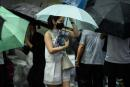 A woman protects her copy of the Apple Daily newspaper's final issue from the rain after queueing up to buy it from a newsstand in Hong Kong on June 24, 2021, after Apple Daily was forced to close under a new national security law, ending a 26-year run of taking on China's authoritarian leaders. / AFP / Anthony WALLACE