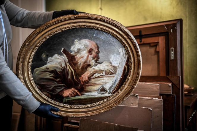 Paris, 25mars 2021 : un manutentionnaire tient un tableau du peintre français Jean-Honoré Fragonard représentant un «Philosophe lisant» (vers 1768-1770).
