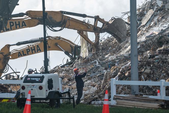 Des membres de l'équipe de recherche et de sauvetage cherchent d'éventuels survivants dans l'immeuble de douze étages partiellement effondré, à Surfside, en Floride,le 27 juin 2021