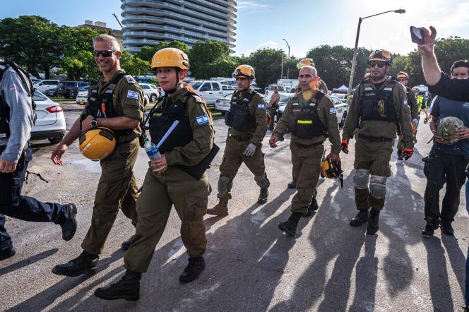 Les membres de la délégation des sauveteurs israéliens se rassemblent à leur arrivée dans la zone proche de l'immeuble partiellement effondré de Surfside, en Floride, le 27 juin 2021.
