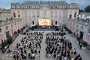 """People sit as they keep social distance while listening to electronic music performer Irene Dresel during France's annual """"la Fete de la Musique"""" festival in the courtyard of the presidential Elysee Palace in Paris, France June 21, 2021. Ian Langsdon/Pool via REUTERS"""
