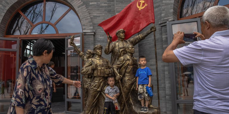 epa09265430 Boys pose for photos next to a revolutionary monument on the newly opened red-themed pedestrian street in Yan'an, Shaanxi province, China, 12 June 2021. Wanda Group on the occasion of the centenary anniversary of the Chinese Communist Party (CCP) has opened on 12 June the revolutionary-themed area, on which they spent 12 billion yuan (around 1.54 billion euros). The red-themed complex of 1.28 square kilometers in size has a Red Street, shops, restaurants, galleries, hotels, a theatre, and a lake, among other facilities, which were built in the revolution period style. Being China's Communist Party revolutionary birthplace, Yan'an city is one of the most famous places for millions of people doing 'Red Tourism,' which focuses on the historically important locations for the Communist Party, battlefield sites, and residences of important past communist leaders. The Chinese Communist Party will mark the 100th anniversary of its founding on 01 July 2021.  EPA/ROMAN PILIPEY (MaxPPP TagID: epalivefive550151.jpg) [Photo via MaxPPP]