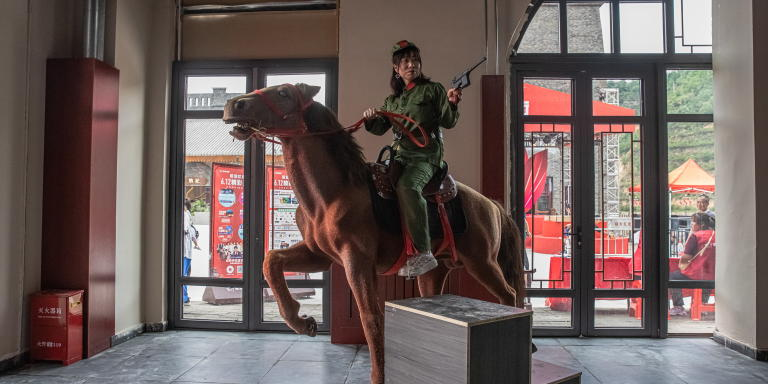 epa09265455 A woman wearing a Red Army uniform poses for photos in a photo studio on the newly opened red-themed pedestrian street in Yan'an, Shaanxi province, China, 12 June 2021. Wanda Group on the occasion of the centenary anniversary of the Chinese Communist Party (CCP) has opened on 12 June the revolutionary-themed area, on which they spent 12 billion yuan (around 1.54 billion euros). The red-themed complex of 1.28 square kilometers in size has a Red Street, shops, restaurants, galleries, hotels, a theatre, and a lake, among other facilities, which were built in the revolution period style. Being China's Communist Party revolutionary birthplace, Yan'an city is one of the most famous places for millions of people doing 'Red Tourism,' which focuses on the historically important locations for the Communist Party, battlefield sites, and residences of important past communist leaders. The Chinese Communist Party will mark the 100th anniversary of its founding on 01 July 2021.  EPA/ROMAN PILIPEY (MaxPPP TagID: epalivefive550174.jpg) [Photo via MaxPPP]