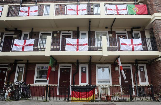 Un drapeau allemand et deux portugais figurent parmi les drapeaux anglais qui ornent les balcons et les paliers du lotissement Kirby à Londres, le mardi 29 juin 2021.