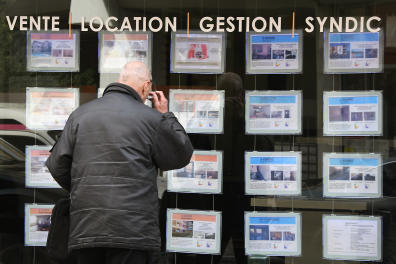 A pedestrian looks at notices of properties for sale in an estate agents premises on a street in Toulouse on March 15, 2018. (Photo by PASCAL PAVANI / AFP)