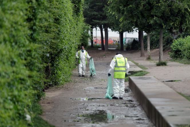 Des agents municipaux nettoient une allée du Jardin d'Eole, au nord-est de Paris, le 30juin 2021.