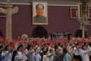People wave Chinese flags beneath a large portrait of the late leader Mao Zedong during a ceremony to mark the 100th anniversary of the founding of the ruling Chinese Communist Party at Tiananmen Gate in Beijing Thursday, July 1, 2021. (AP Photo/Ng Han Guan)