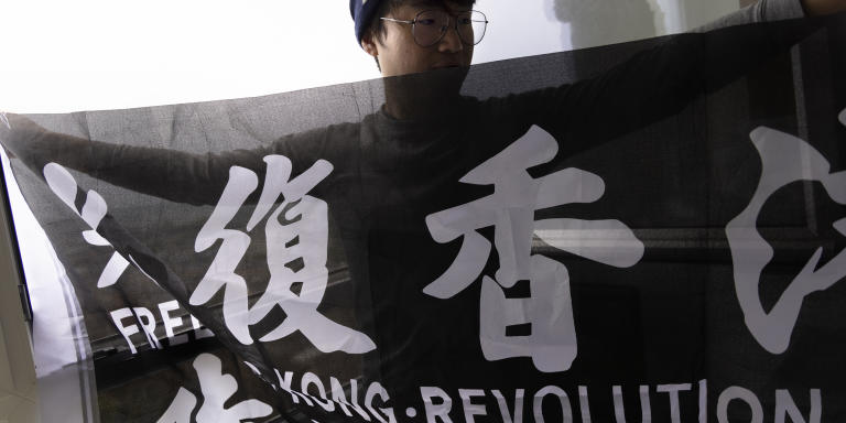 """Simon Cheng, 30, a Hong Kong activist, has been living in exile in the UK since November 30, 2019. He was detained by Chinese authorities in August 2019 upon his return from a business trip in Shenzhen. Cheng is photographed in his residence in London on June 27, 2021. Cheng is photographed holding a black """"Free Hong Kong, Revolution Now"""" flag, which is officially banned in Hong Kong."""