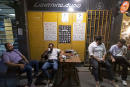 """Iranian youths sit at a coffee shop in downtown Tehran on June 20, 2021. - Iran's ultraconservatives hailed the election victory of their candidate Ebrahim Raisi, after Washington charged the vote was unfair and Tehran's arch-foe Israel labelled him the """"most extremist"""" president yet. Raisi, 60, won this week's election in which more than half the voters stayed away after many political heavyweights had been barred from running and as an economic crisis driven by US sanctions has battered the country. (Photo by MORTEZA NIKOUBAZL / AFP)"""