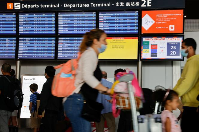 Des passagers attendent devant les écrans annonçant les vols et la grève des employés d'ADP, à l'aéroport Roissy-Charles deGaulle le 3 juillet 2021.