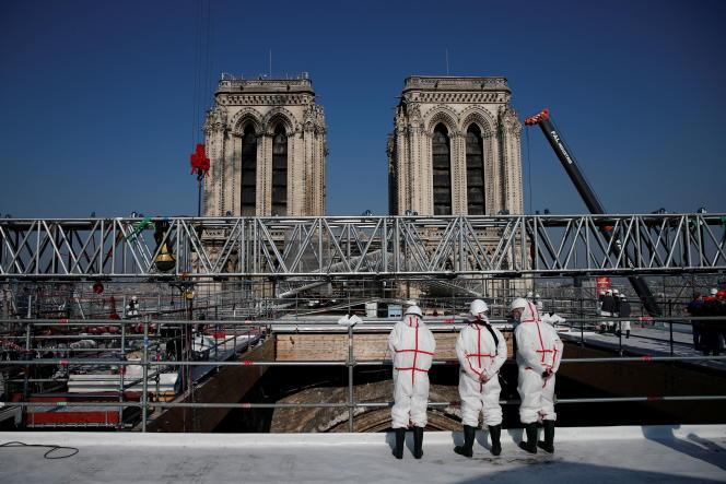 Des ouvriers en tenue de protection se tiennent sur les toits de la cathédrale Notre-Dame à Paris, le 15 avril 2021.