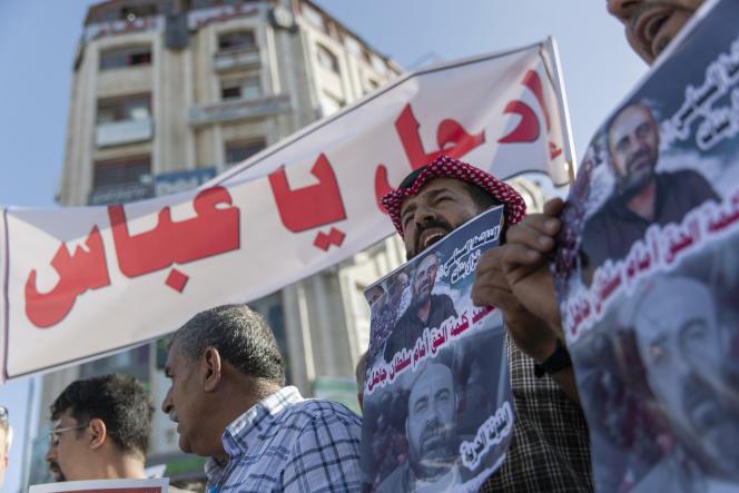 Des manifestants brandissent des photos de Nizar Banat, un critique virulent de l'Autorité palestinienne, et une banderole mentionnant«Abbas, pars», lors d'un rassemblement suivant la mort de M. Banat, à Ramallah, le 3 juillet 2021.