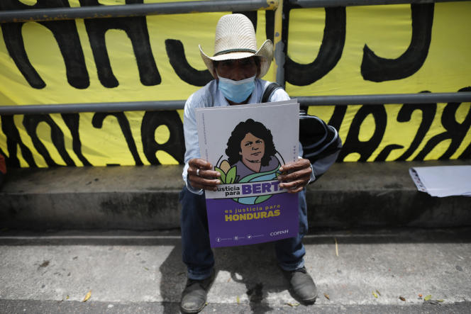 A supporter of slain Honduran environmental and Indigenous rights activist Berta Caceres holds a flyer with her image calling for justice, during a protest as the trial against Roberto David Castillo Mejia goes on in Tegucigalpa, Honduras, Monday, July 5, 2021. A court has unanimously found Castillo Mejia guilty of participating in the killing of Caceres, who was shot by armed men at her home on March 3, 2016, considering him the mastermind of the crime. (AP Photo/Elmer Martinez)