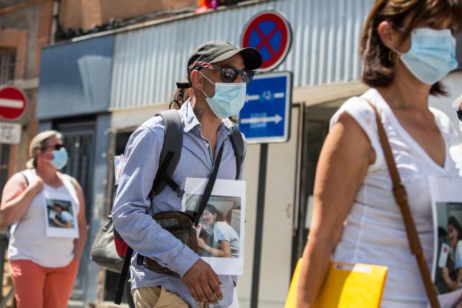Cédric Jubillar, principal suspect dans la disparition de son épouse Delphine, tient sa photo lors d'un rassemblement à Albi, le 12 juin 2021.