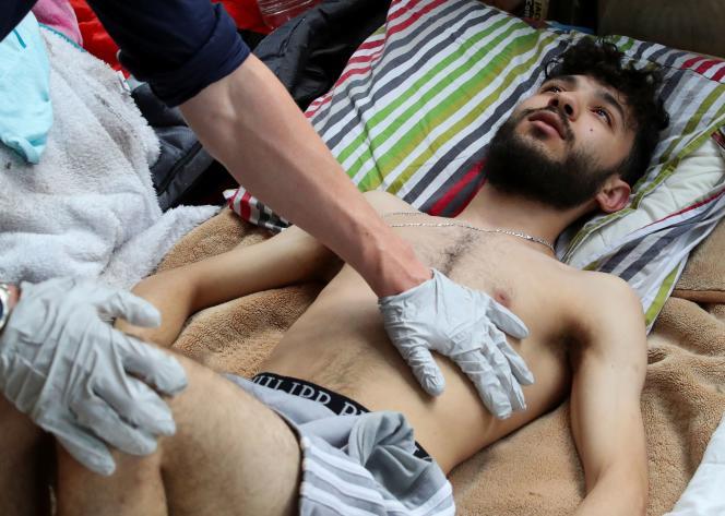 Nassr Eddine Tssouli, 20 ans, demandeur d'asile, est aidé par un infirmier, alors qu'il participe à une grève de la faim depuis plus d'un mois, sur le campus de l'université belge ULB-VUB, à Bruxelles, le 6 juillet 2021.
