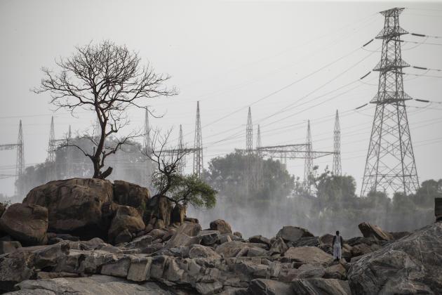 Un homme se tient sur des rochers près du barrage de Roseires, au Soudan, le 21 juin 2021. Les barrages qui produisent de l'électricité ne couvrent que 40 % des besoins du Soudan.