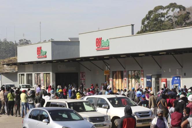 Plusieurs dizaines de personnes font la queue devant un supermarché à Mbabane, la capitale de l'Eswatini, le 1er juillet 2021.